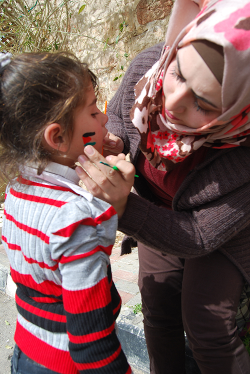 A woman paints a Palestinian flag on a child - Derek Smallwood